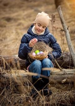 Menina feliz e sorridente sentada em um tronco de árvore na floresta com uma cesta de páscoa