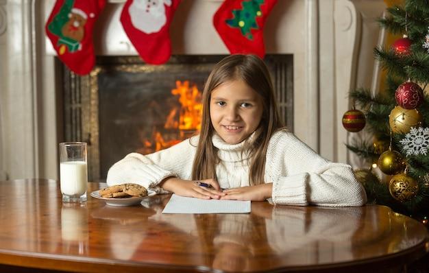 Menina feliz e sorridente sentada perto da lareira e escrevendo uma carta para o papai noel