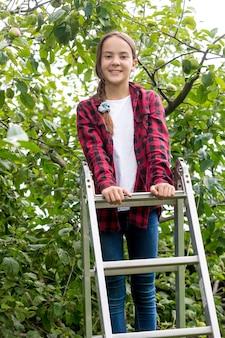 Menina feliz e sorridente subindo na escada do jardim