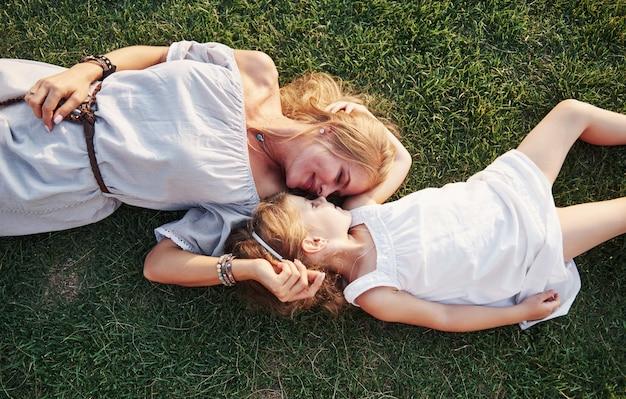 Menina feliz e sua mãe se divertindo ao ar livre na grama verde em dia de verão ensolarado