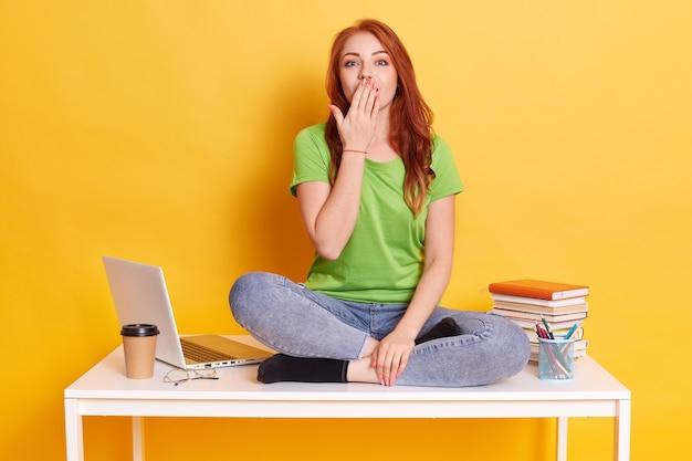 Menina feliz e surpresa, que não consegue acreditar em triunfo ou sucesso inesperado, cobre a boca com a palma da mão, usa camiseta e jeans verdes, posa contra a parede amarela do estúdio