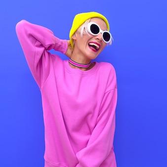 Menina feliz elegante em acessórios de moda. gorro, óculos de sol e gargantilha. vibrações coloridas da moda