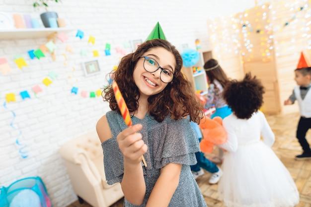 Menina feliz em copos com pirulito colorido