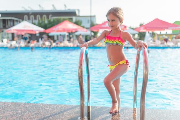 Menina feliz em fato de banho colorido na piscina