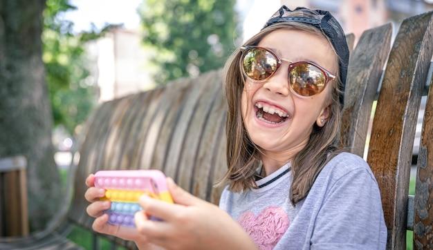Menina feliz em óculos de sol com um smartphone em um caso moderno abri-lo.