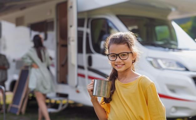 Menina feliz em pé ao ar livre e olhando para a câmera de carro de caravana, viagem de férias em família.