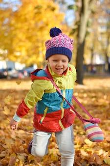 Menina feliz em roupas brilhantes, brincando com folhas em um parque da cidade no outono