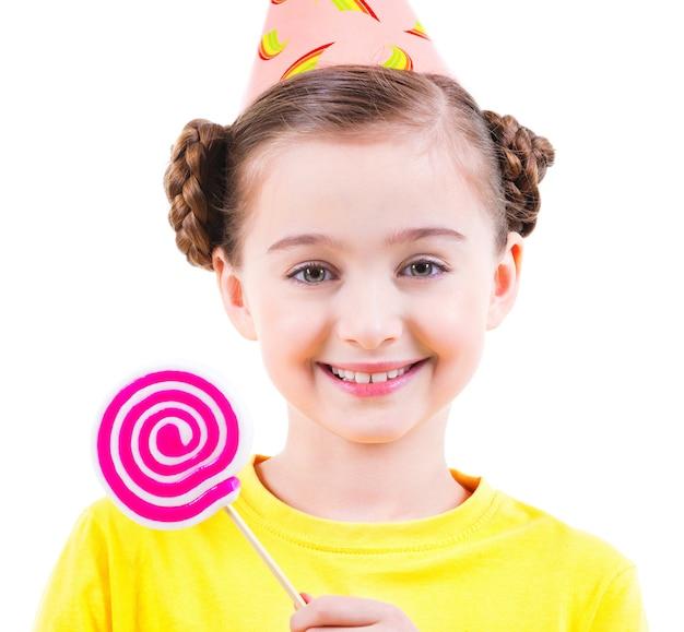 Menina feliz em t-shirt amarela e chapéu de festa segurando doces coloridos - isolado no branco.