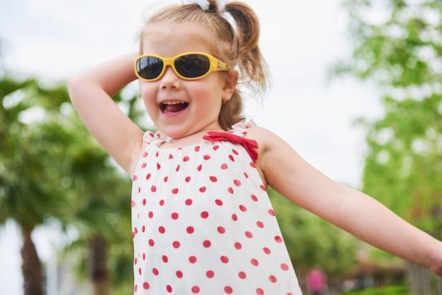 Menina feliz em um óculos de sol de verão.