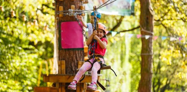 Menina feliz em um parque de corda na madeira