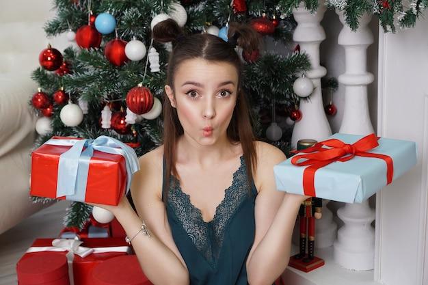Menina feliz em um penhoar verde e penteado engraçado segurando duas caixas de presente sem saber qual presente escolher para dar a um quarto decorado com árvore de natal