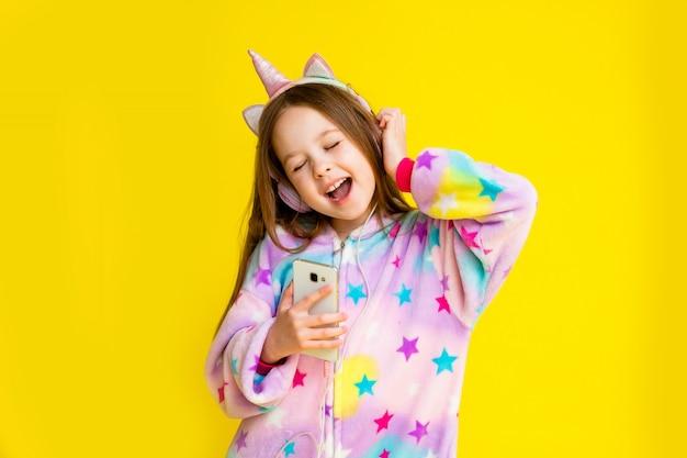 Menina feliz em um unicórnio kigurumi em um fundo amarelo