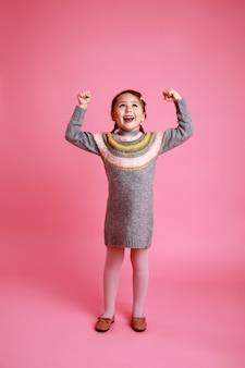 Menina feliz em um vestido quente, mostrando sua força no fundo rosa