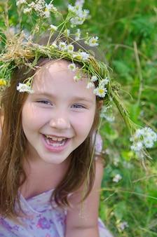 Menina feliz em uma guirlanda de flores do campo no prado