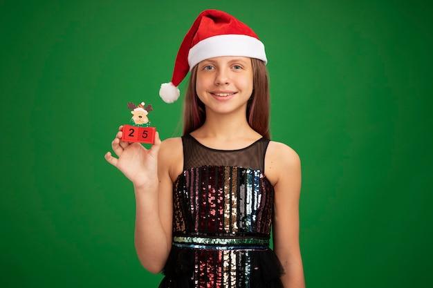 Menina feliz em vestido de festa glitter e chapéu de papai noel mostrando cubos de brinquedo com data 25 sorrindo alegremente em pé sobre um fundo verde