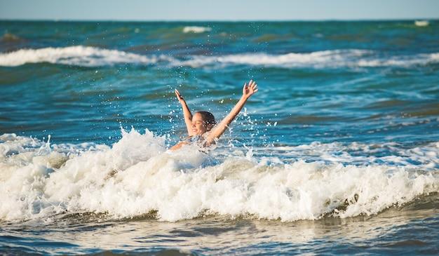 Menina feliz emocional se banha nas ondas do mar tempestuoso e espumoso em um dia ensolarado de verão quente. o tão esperado conceito de férias e viagens com crianças