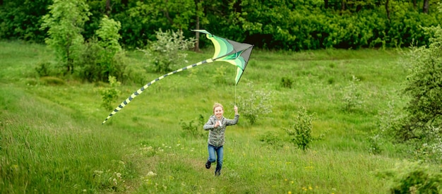 Menina feliz empinando pipa brilhante ao ar livre na natureza na primavera