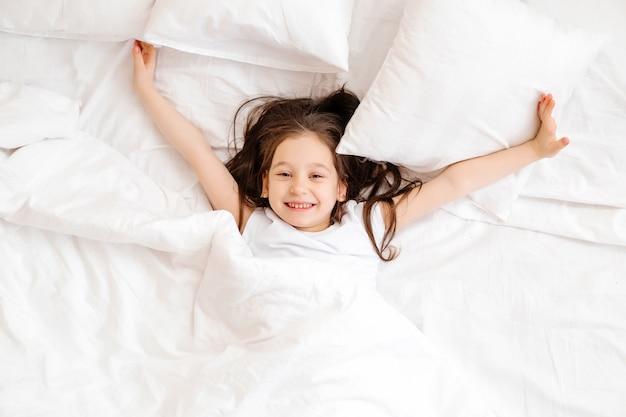 Menina feliz encontra-se na cama em casa de manhã. sono saudável do bebê. roupa de cama branca, espaço para texto