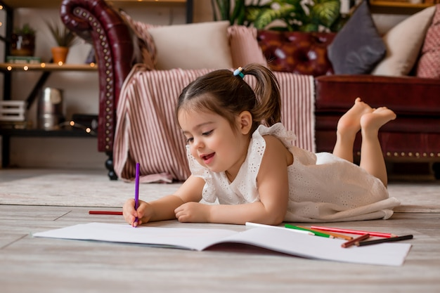 Menina feliz encontra-se no chão da casa e desenha com lápis de cor. desenvolvimento infantil. ficar em casa