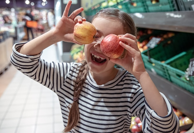 Menina feliz escolhe maçãs em uma mercearia.