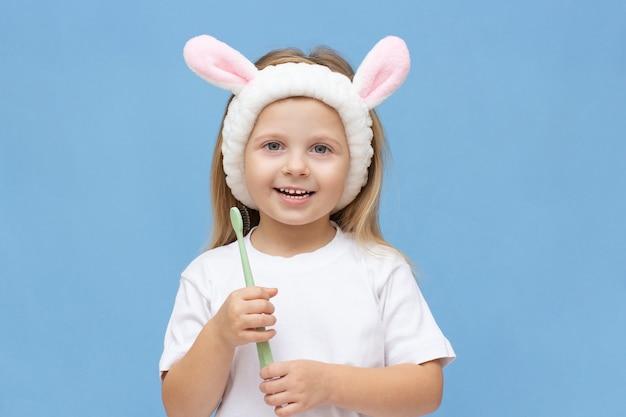 Menina feliz escovando os dentes com uma escova de dentes e sorrindo sobre um fundo azul. polegar para cima