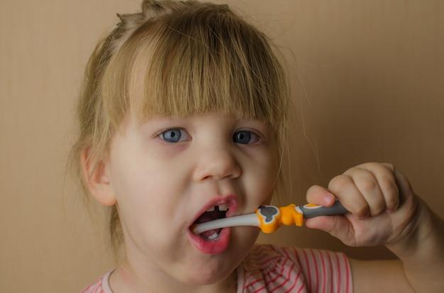 Menina feliz escovando os dentes. espaço da cópia