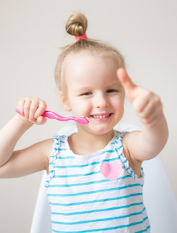 Menina feliz, escovar os dentes, escova de dentes-de-rosa, higiene dental, manhã noite conceito saudável estilo de vida