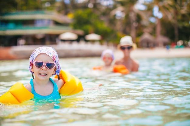 Menina feliz espirrando água turquesa. mãe com menina nadando no mar