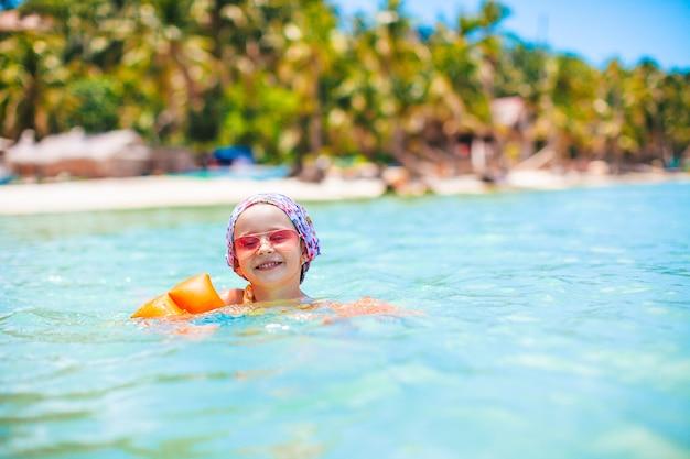 Menina feliz espirrando água turquesa