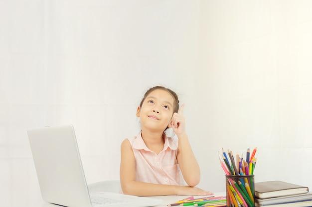 Menina feliz está sentado à mesa e pensando