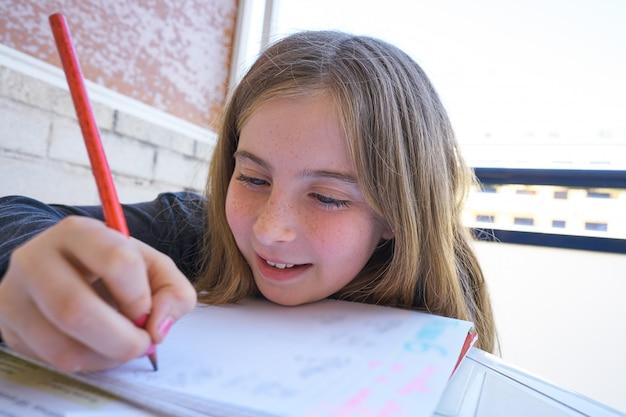 Menina feliz estudante fazendo sua lição de casa