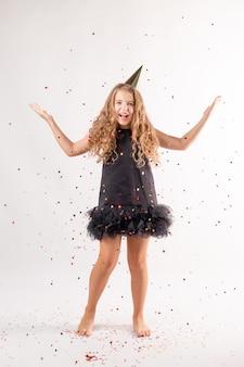 Menina feliz explodindo confetes em um fundo branco