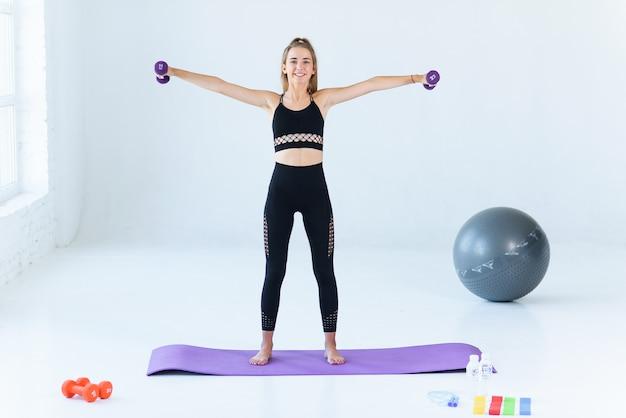 Menina feliz fitness praticando esportes fazendo pesos em casa