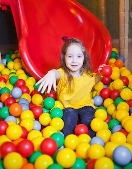 Menina feliz jogando e se divertindo no jardim de infância com bolas coloridas no play center