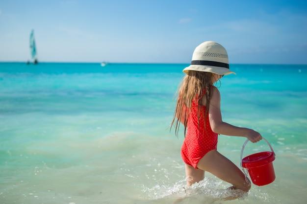 Menina feliz jogando na praia durante as férias do caribe