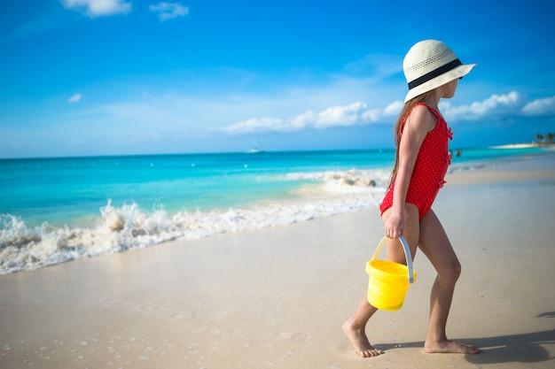 Menina feliz jogando na praia durante férias nas caraíbas