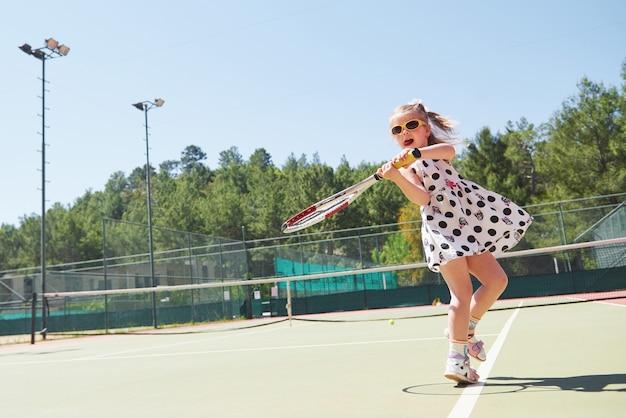 Menina feliz jogando tênis. esporte de verão