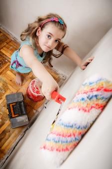 Menina feliz jovem adolescente está pintando uma parede em seu quarto