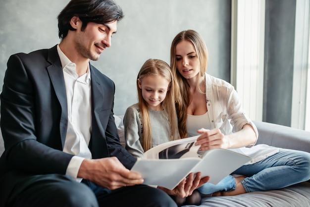 Menina feliz lendo um livro com os pais em casa