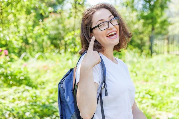 Menina feliz linda estudante positivo em óculos com mochila sorrindo no parque verde. mulher descansando no campus durante a pausa para o almoço. conceito de educação e lazer.