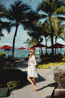 Menina feliz modelo de biquíni posando sob as palmeiras no território do luxuoso resort na t ...