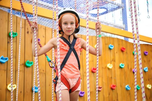 Menina feliz na maneira da corda no centro de diversões para crianças.