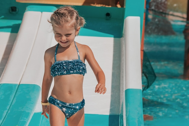 Menina feliz na piscina ao ar livre