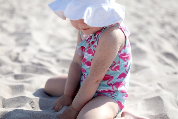 Menina feliz na praia de areia branca, aproveitando o verão e as férias.