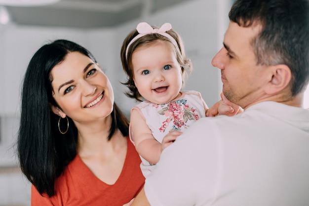 Menina feliz no abraço dos pais, retrato em close-up