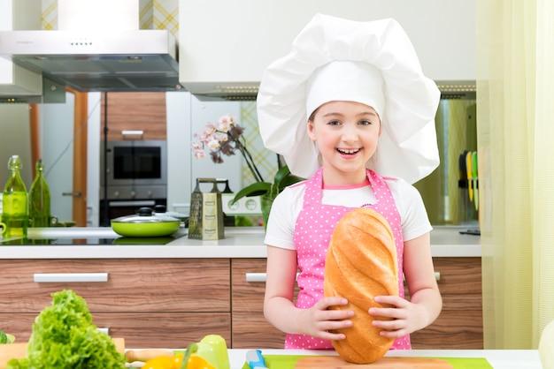 Menina feliz no avental rosa com pão nas mãos na cozinha.