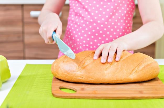 Menina feliz no avental rosa, cortando pão na cozinha.