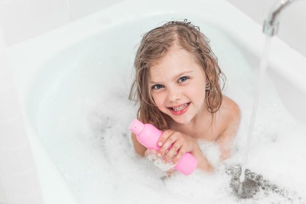 Menina feliz no banheiro com espuma e com frascos de shampoo