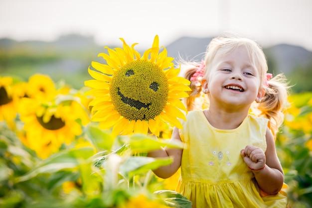 Menina feliz no campo de girassóis no verão. linda garotinha em girassóis