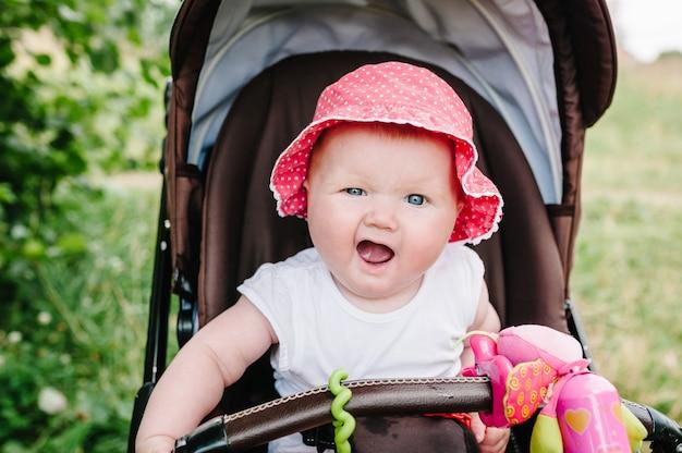 Menina feliz no carrinho de bebê que joga no carrinho de bebê na natureza do fundo.